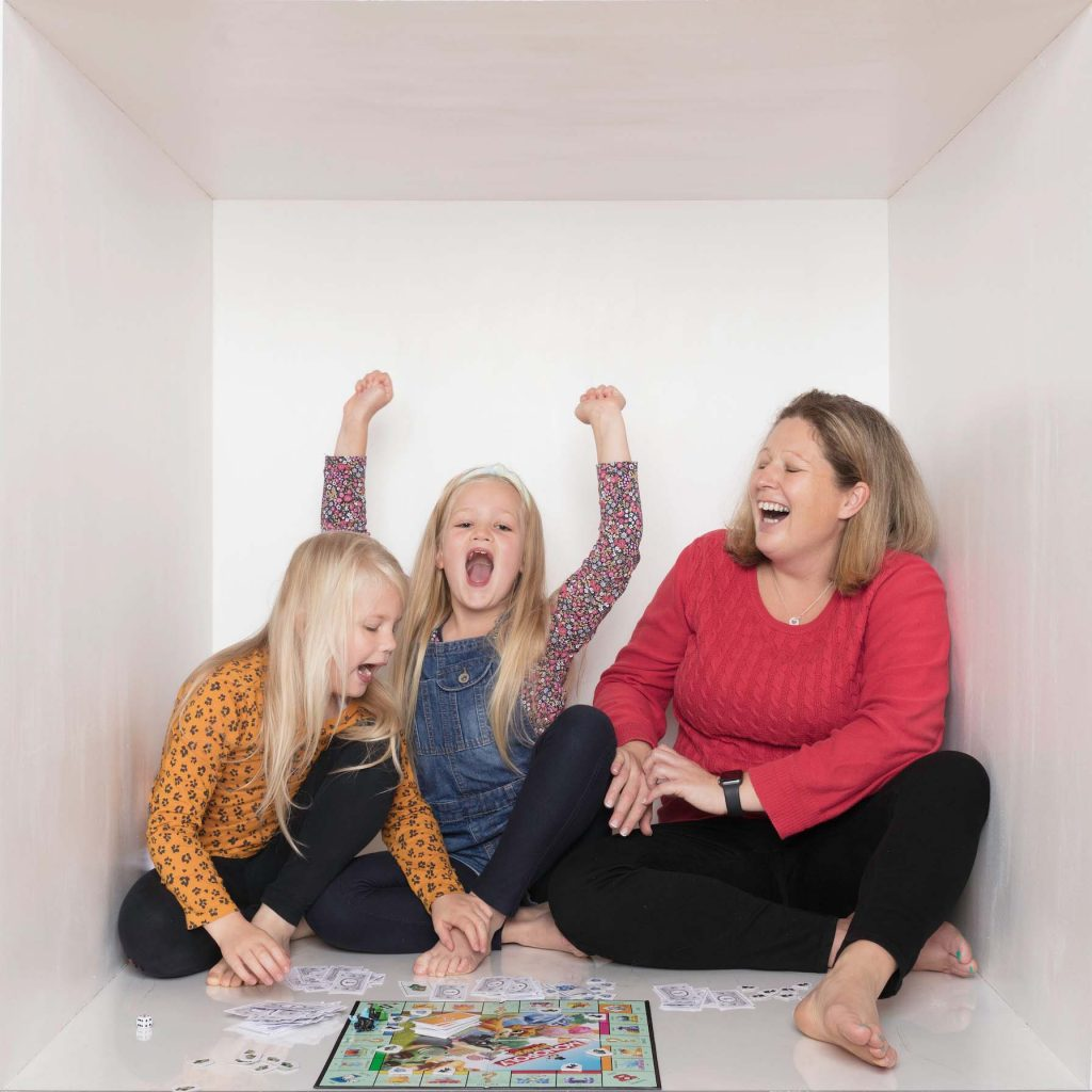 mum and twin girls playing monopoly